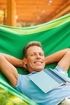 Tellement bon de ne rien faire. heureux homme mûr dormant en position couchée dans un hamac avec un livre posé sur son torse