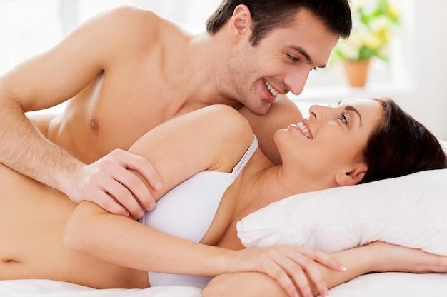 Tellement bon de se réveiller ensemble ! beau jeune couple d'amoureux allongé dans son lit et se regardant avec le sourire