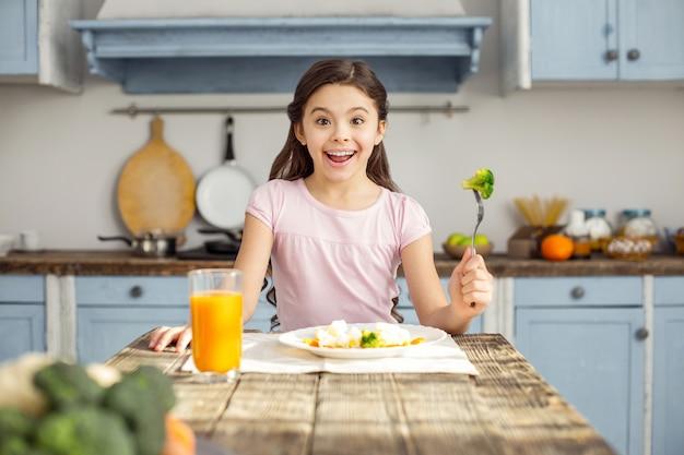 Tellement délicieux. beau contenu petite fille brune souriante et prendre un petit-déjeuner sain et boire du jus