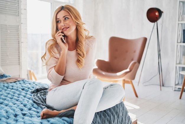 Tellement heureux de vous entendre! jolie jeune femme parlant sur son téléphone intelligent et souriante assise sur le lit à la maison