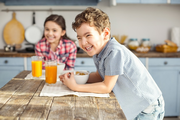 Tellement joyeux. beau petit garçon aux cheveux noirs ravi de rire et de prendre un petit-déjeuner sain avec sa sœur et la jeune fille souriante dans le