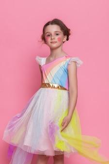 Tellement mignon, adorable et drôle ! portrait d'une belle fille douce vêtue d'une robe bleu clair, elle rêve de confiserie et de pâtisserie, isolée sur fond rose vif