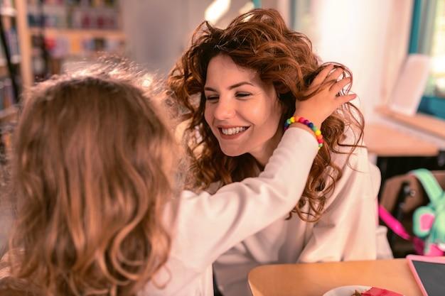Tellement mignon. femme heureuse en gardant le sourire sur son visage tout en regardant son enfant