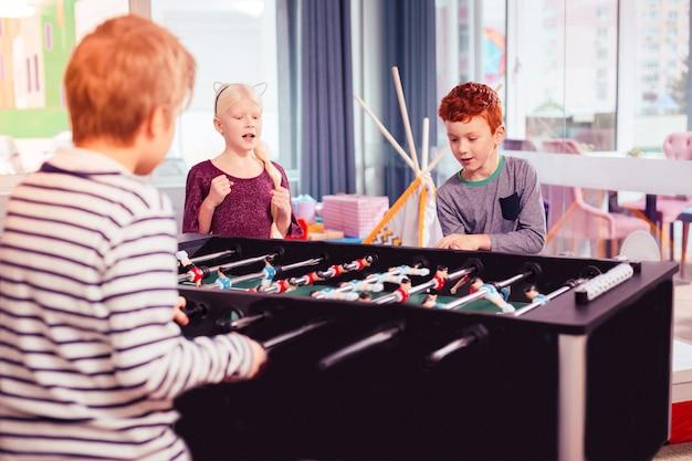 Tellement occupés. deux charmants enfants jouant au jeu et une fille blonde interrompant le football kicker