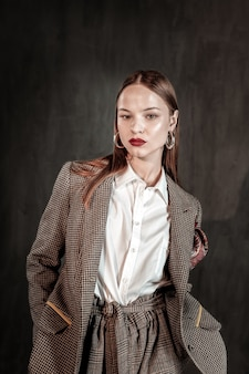 Tellement sérieux. modèle ravi debout sur un mur gris et démontrant un costume élégant