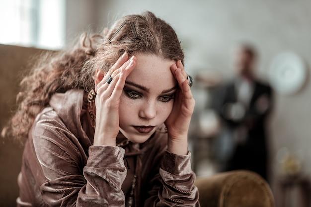 Tellement stressé. fille bouclée portant des bagues et maquillée sombre se sentant stressée après la rupture avec son petit ami