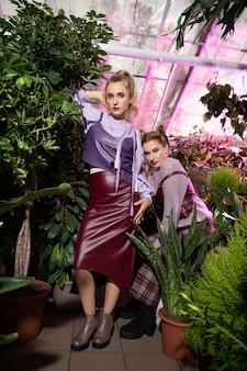 Tellement vert. jolies femmes élégantes debout parmi les plantes vertes tout en ayant une séance photo