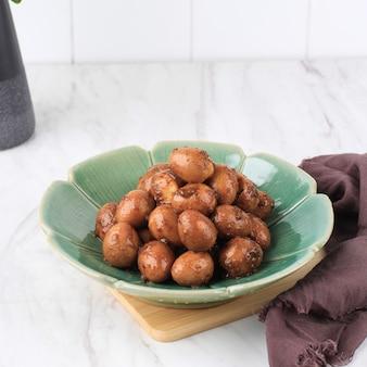 Telur puyuh bumbu petis ou œuf de caille épicé avec pâte de crevettes, nourriture typique de l'est de java en indonésie qui est généralement servi à l'aïd fitr lebaran avec ketupat.