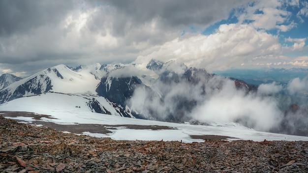 Tempête de neige au sommet d'une montagne. magnifique paysage dramatique avec de grands sommets enneigés au-dessus de nuages bas. les grands sommets atmosphériques des montagnes enneigées dans un ciel nuageux.