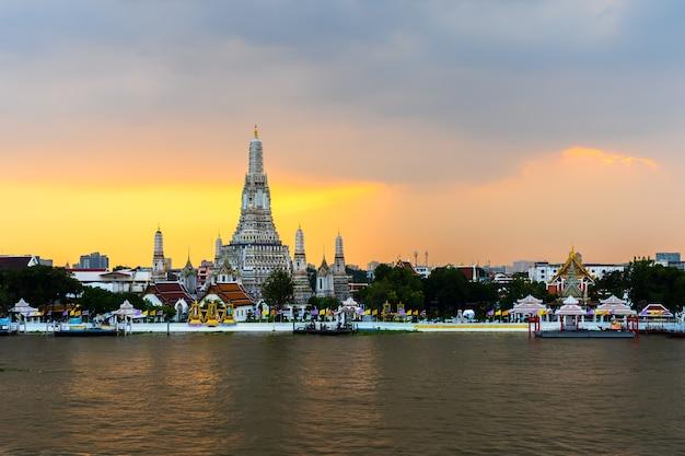 Temple wat arun avec rivière chao phraya au coucher du soleil à bangkok, thaïlande