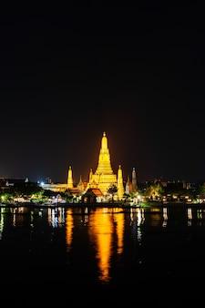 Temple wat arun avec rivière chao phraya la nuit à bangkok, thaïlande