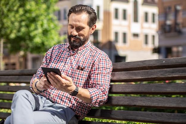 Temps agréable. heureux homme adulte lisant son livre électronique tout en se reposant sur le banc