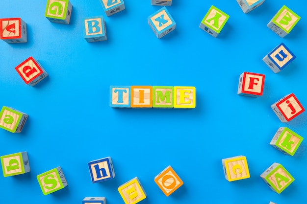 Temps. blocs d'alphabet coloré en bois sur bleu