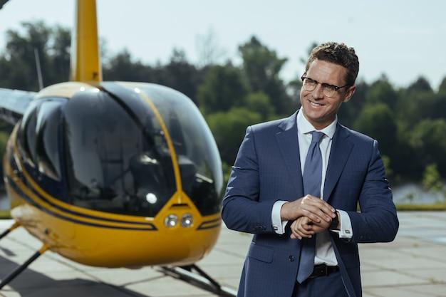 À temps. cheerful young executive smiling après avoir vérifié la montre en se tenant debout sur un héliport et en attendant un tour en hélicoptère