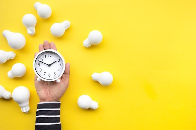 Temps, date et créativité à plat avec une main masculine tenant une horloge avec ampoule