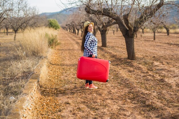 Temps de détente, de voyage et de vacances concept - jeune femme avec valise rouge dans la nature de l'été