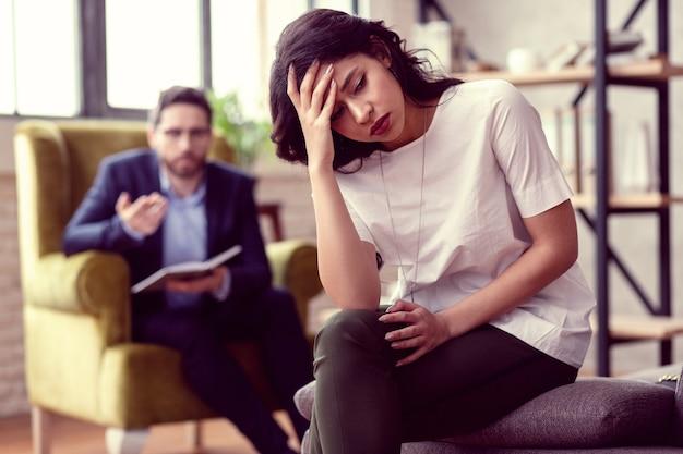 Temps difficiles. belle jeune femme se sentant déprimée tout en se concentrant sur ses problèmes