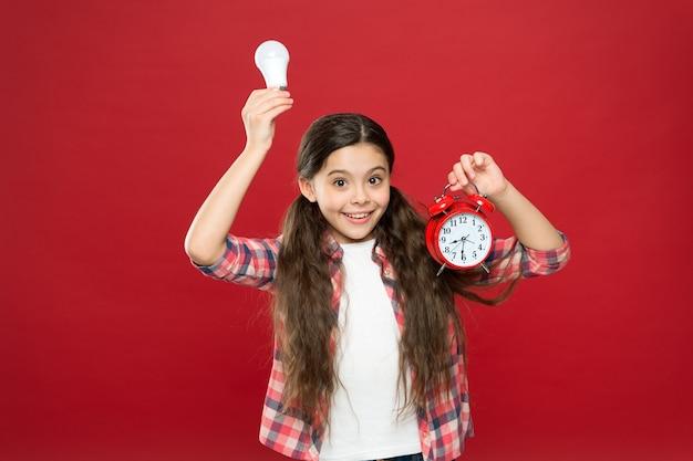 Temps d'éclairage. idée et inspiration. il est temps de trouver l'inspiration. ampoule et horloge de petite fille. sonnez l'alarme et allumez la lampe. brainstorming et gestion du temps. l'énergie électrique. idée d'affaires.