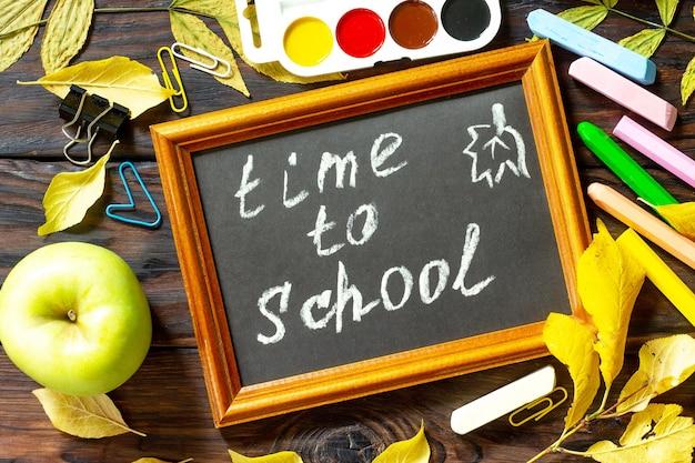 Temps à l'école concept de retour à l'école contexte de l'éducation avec des fournitures scolaires et une pomme