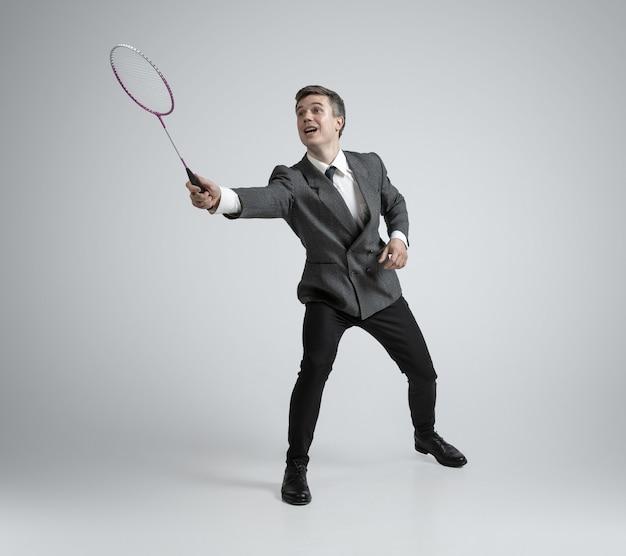 Le temps des émotions. homme en tenue de bureau jouant au badminton sur fond gris