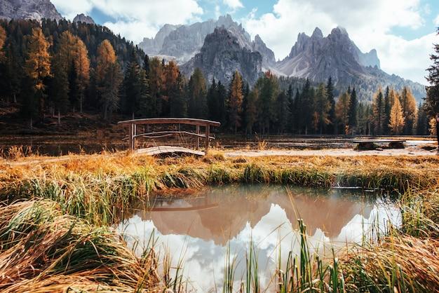 Temps ensoleillé. vue imprenable sur les montagnes majestueuses avec des bois en face d'eux au jour de l'automne. flaque d'eau qui part du lac avec petit pont au centre