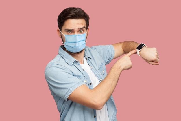 Le temps est écoulé. portrait d'un jeune homme sérieux avec un masque médical chirurgical en chemise bleue debout et regardant la caméra, pointant sur sa montre intelligente. tourné en studio intérieur, isolé sur fond rose.