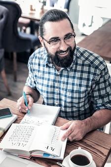 Le temps d'étudier. enthousiaste homme d'affaires barbu portant des lunettes se sentant excité à étudier une langue étrangère
