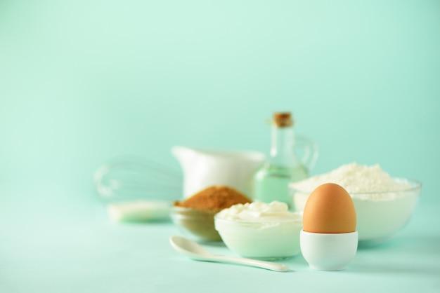 Temps de faire cuire. ingrédients de cuisson - beurre, sucre, farine, œufs, huile, cuillère, pinceau, fouet, lait sur fond bleu.