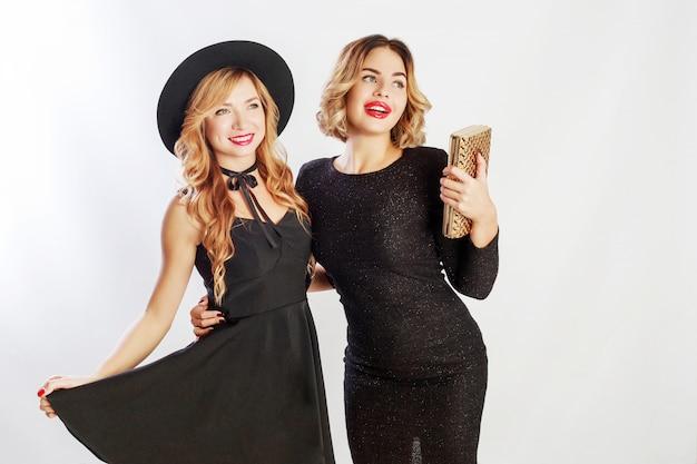 Temps de fête de deux meilleurs amis, femmes blondes en robe élégante de cocktail noir posant en studio sur fond blanc.