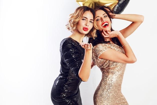 Temps de fête de deux meilleurs amis en robe élégante de cocktail posant en studio sur fond blanc. confettis dorés étincelants. coiffure ondulée ballons de fête.