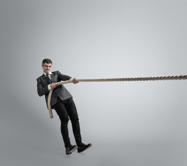 Le temps de la force. homme en vêtements de bureau s'entraînant avec des cordes sur un mur gris. obtenez la cible, surmontez les problèmes, les délais. homme d'affaires en mouvement, action. sport, mode de vie sain, travail.