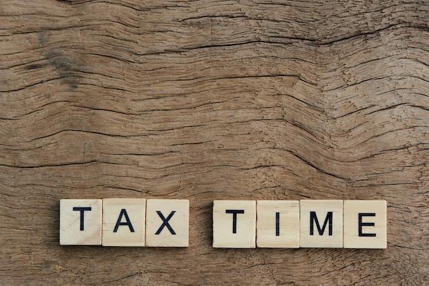 Temps d'impôt avec des blocs de l'alphabet en bois, sur fond de bois de planche avec espace de copie