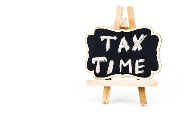 Temps d'impôt écrit sur tableau sur fond blanc.