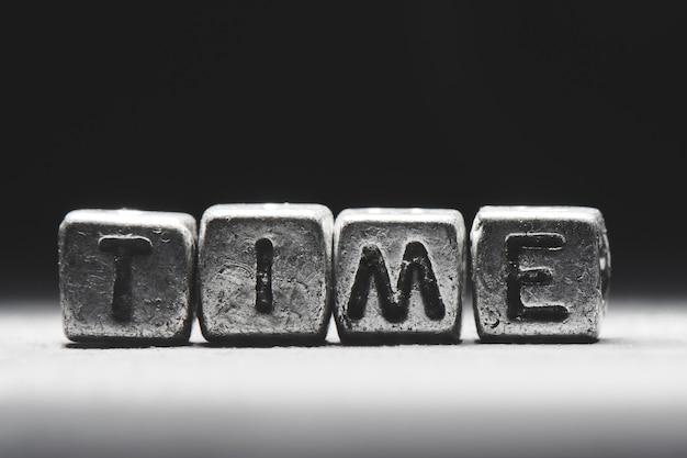 Temps d'inscription 3d sur des cubes de métal sur un fond gris noir close-up isolé