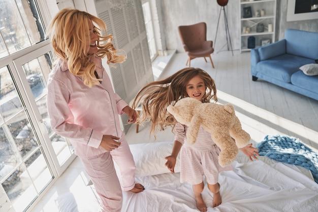 Temps libre ensemble. vue de dessus d'une jolie petite fille sautant sur le lit avec sa mère tout en passant du temps à la maison