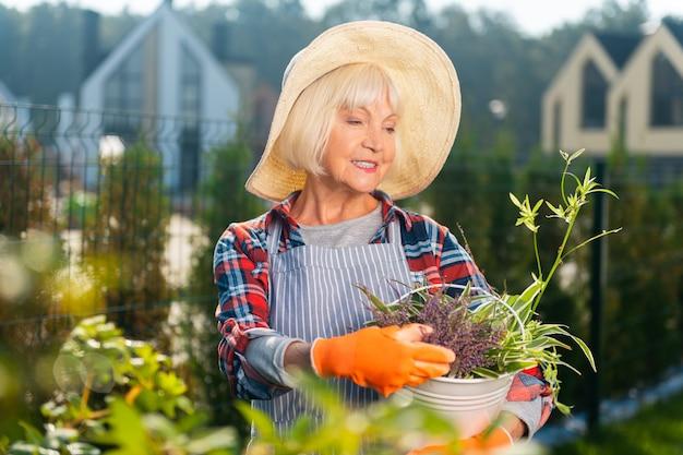 Temps libre. jolie vieille dame se sentant bien tout en passant une journée dans le jardin