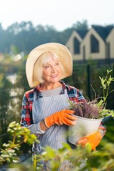 Temps libre. sourire jolie vieille femme souriante tout en passant une journée à l'extérieur