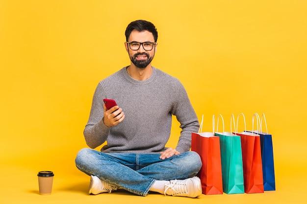 Temps de magasinage à domicile en ligne! portrait de jeune homme barbu assis sur le sol avec un téléphone mobile avec les jambes croisées avec des sacs à provisions.
