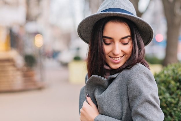 Temps de marche de la ville de la charmante jeune femme élégante en manteau gris, chapeau marchant dans la rue en ville. souriant les yeux fermés, exprimant de véritables émotions de visage positives, style de vie de luxe, perspectives élégantes.