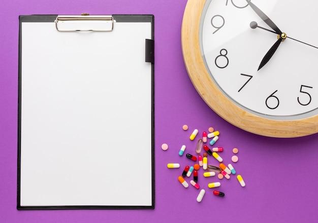 Temps de médicament avec presse-papiers sur table