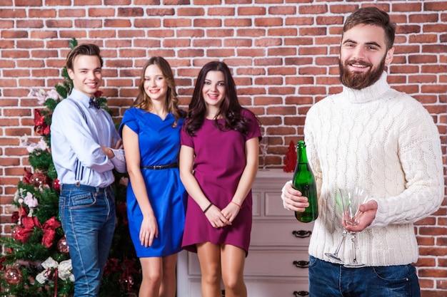Temps de noël avec des amis concept barbu tenant du champagne et deux verres