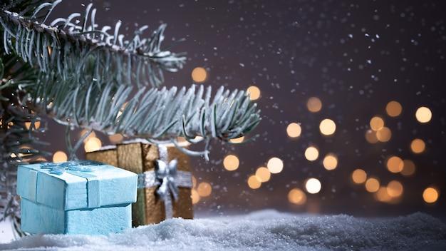Temps de noël et cadeaux avec nuit et lumières. fond de noël avec des chutes de neige, arbre à feuilles persistantes de noël