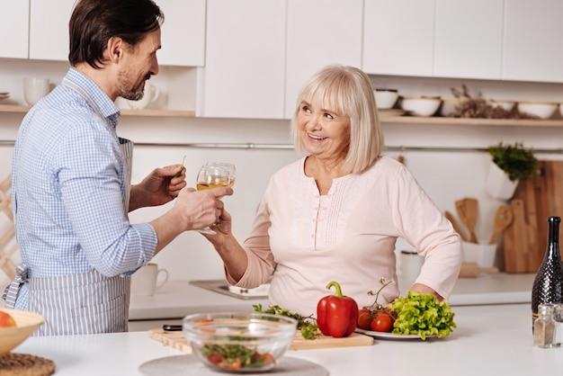 Le temps passe. homme d'âge mûr charismatique positif debout dans la cuisine et célébrer des vacances tout en dégustant un verre de vin avec sa mère vieillissante