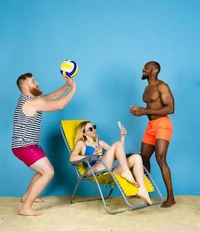 Temps pour l'activité. des amis heureux prennent selfie, jouant au volleyball sur fond bleu de studio. concept d'émotions humaines, expression faciale, vacances d'été ou week-end. chill, été, mer, océan.