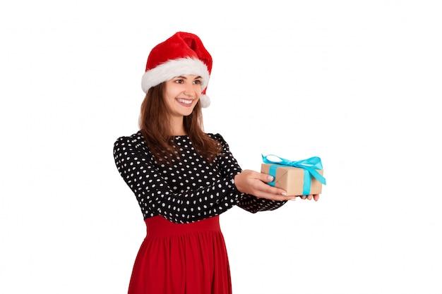 Temps pour les cadeaux, fille souriante au chapeau de noël donne une boîte cadeau, isolée sur blanc,