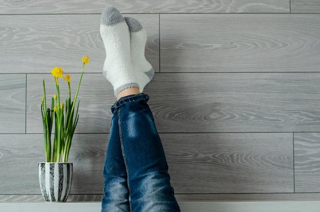 Temps pour se détendre. jambes féminines vers le haut sur le mur et le pot de fleurs avec narcisse.