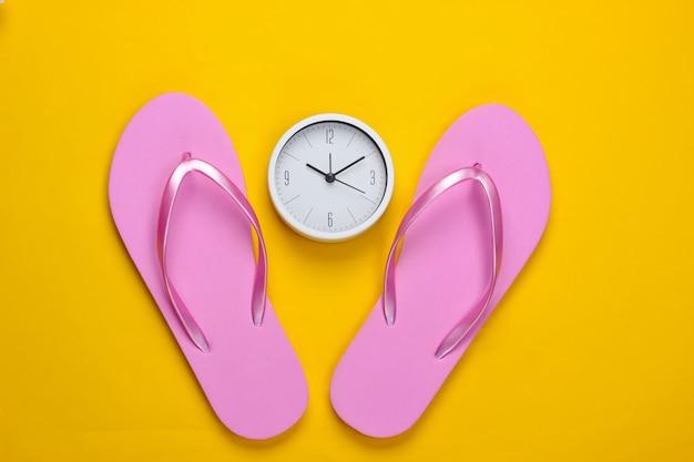 Temps pour des vacances à la plage. tongs avec horloge sur une surface jaune. vue de dessus