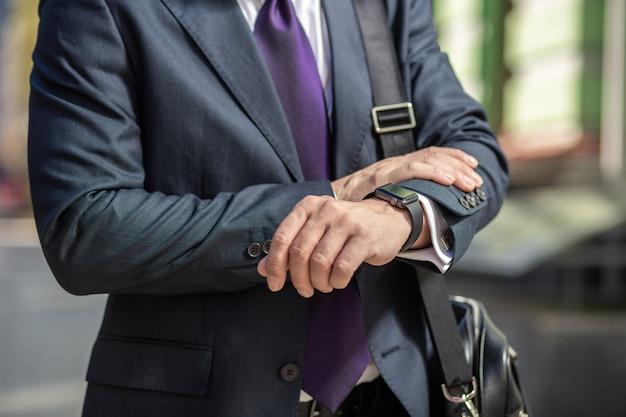 Temps précieux. gros plan d'un homme d'affaires professionnel en regardant sa montre-bracelet à l'extérieur