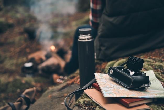 Temps de repos après une longue route. bouchent la vue arrière du jeune homme se réchauffant près du feu de camp alors qu'il était assis dans la forêt