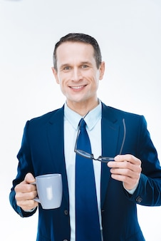 Temps de repos. heureux heureux homme d'affaires positif souriant et appréciant son thé tout en se reposant du travail